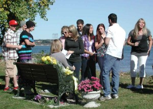 Friends and family gather around a riverside bench dedicated to the memory of Reilly Anzovino.